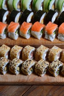 Un coup de macro d'un ensemble de sushi de nombreux rouleaux est situé sur une planche à découper en bois