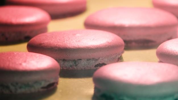 Coup de macro de macaron rose sur une plaque de cuisson