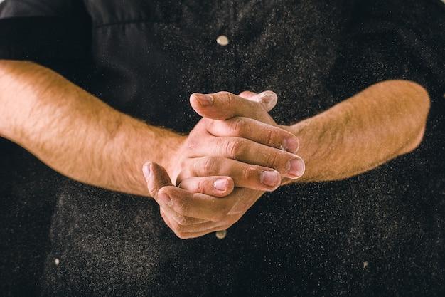 Coup de main et farine blanche sur fond noir