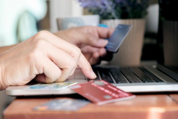 Coup de main de l'homme en tapant sur un ordinateur portable et détenant une carte de crédit, concept de transactions en ligne.
