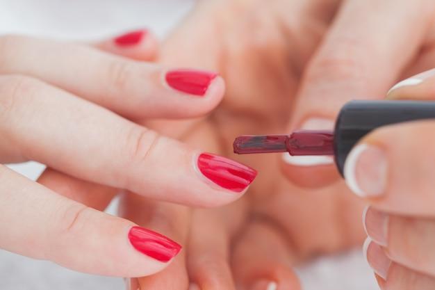 Coup de mains de détails appliquant le vernis à ongles rouge aux ongles