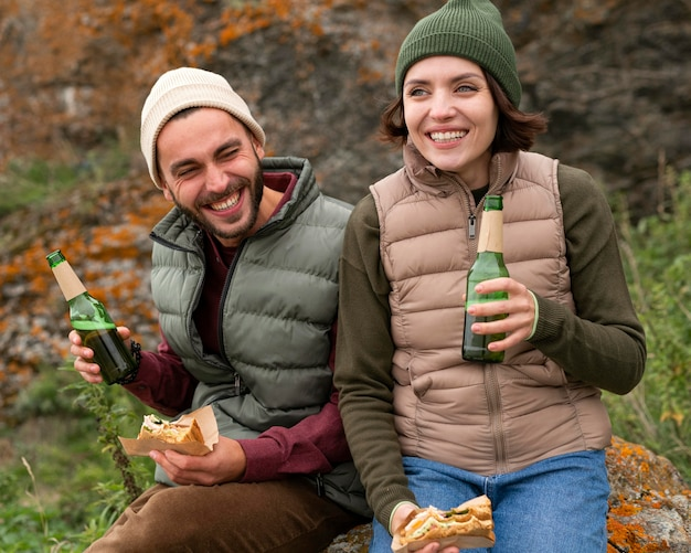 Coup de milieu heureux couple assis sur un rocher et prendre un verre