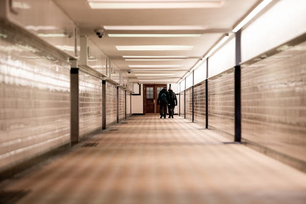 Coup de mise au point peu profonde de deux hommes marchant le long d'un couloir lumineux