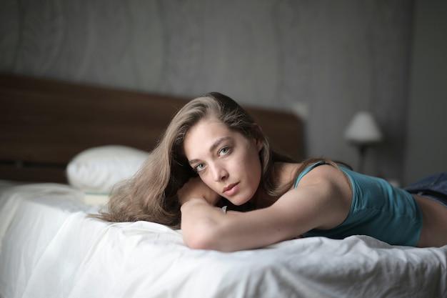 Coup de mise au point peu profonde d'une femme allongée sur le lit