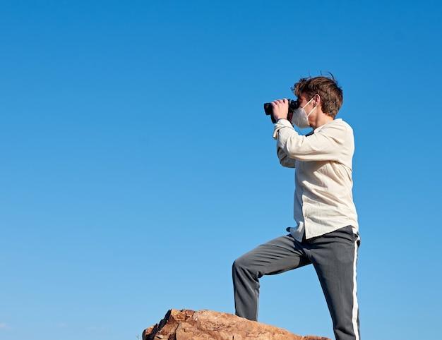 Un coup de mise au point peu profonde d'un jeune homme d'espagne dans une chemise blanche l'observation de la falaise avec des jumelles pendant la pandémie