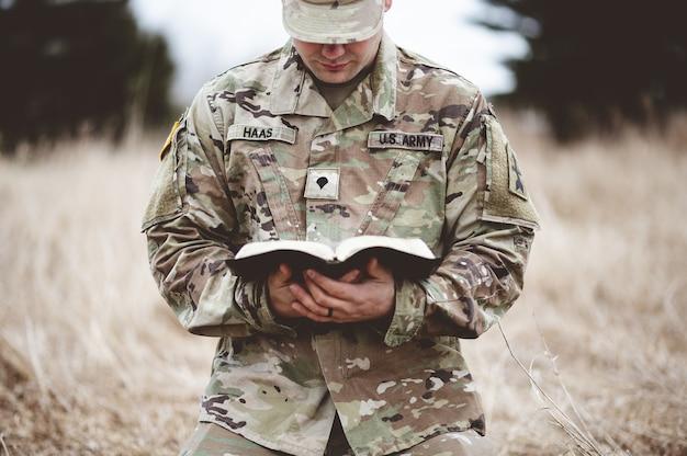 Coup de mise au point peu profonde d'un jeune soldat à genoux sur une herbe sèche en lisant la bible