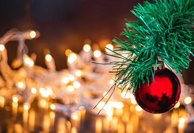 Coup de mise au point sélective d'une boule de noël rouge sur un pin avec des lumières sur l'arrière-plan
