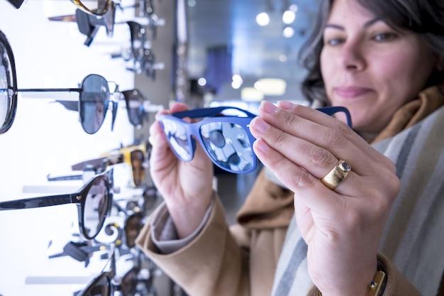 Coup de mise au point sélective d'une femme tenant des lunettes de soleil bleues