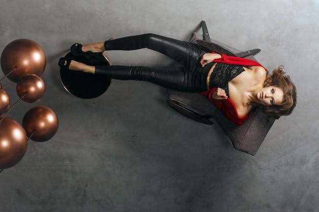 Coup de mode sur toute la longueur d'un modèle séduisant dans des vêtements à la mode. la femme regarde son reflet dans le plafond en miroir