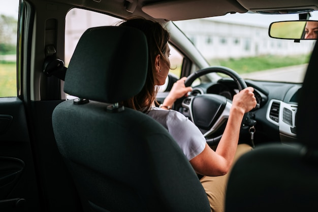 Coup de mode de vie de la jeune femme gaie conduite voiture, vue arrière.
