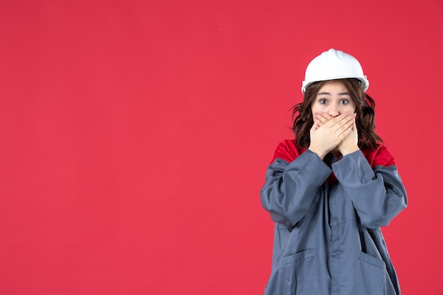 Coup de moitié du corps d'une femme génératrice effrayée en uniforme avec un casque sur fond rouge isolé