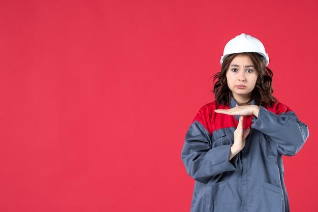 Coup de moitié du corps d'une femme malheureuse en uniforme avec un casque faisant un geste d'arrêt sur fond rouge isolé