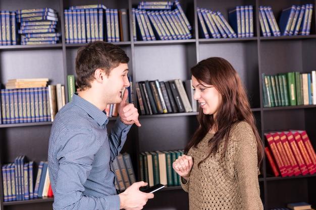 Coup de moitié du corps d'un jeune couple blanc parlant face à face à la mini bibliothèque avec téléphone portable.