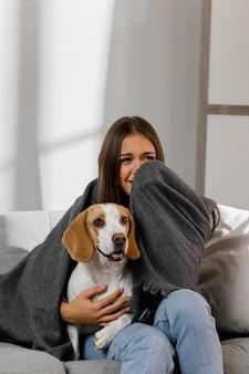 Coup moyen adolescent et chien avec couverture