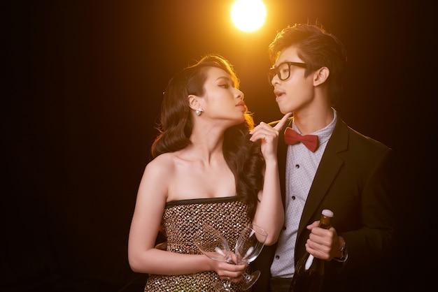 Coup moyen d'un couple enjoué dans le noir avec une bouteille de champagne et des flûtes prêtes à célébrer