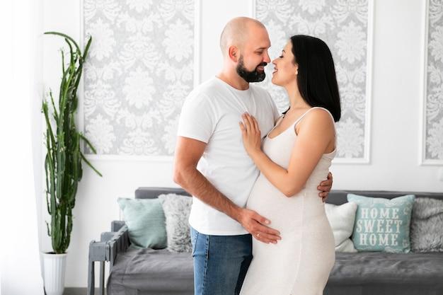Coup moyen couple heureux attend leur bébé