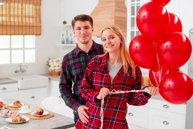 Coup moyen couple heureux avec des ballons