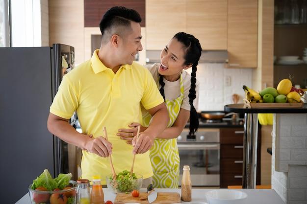 Coup moyen couple heureux dans la cuisine la