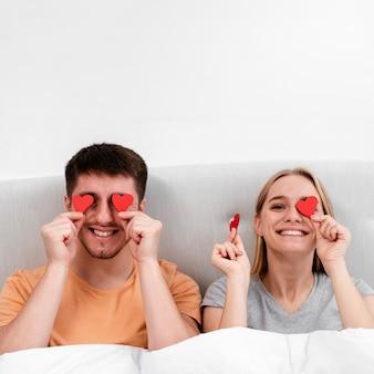 Coup moyen couple heureux avec du papier en forme de coeur