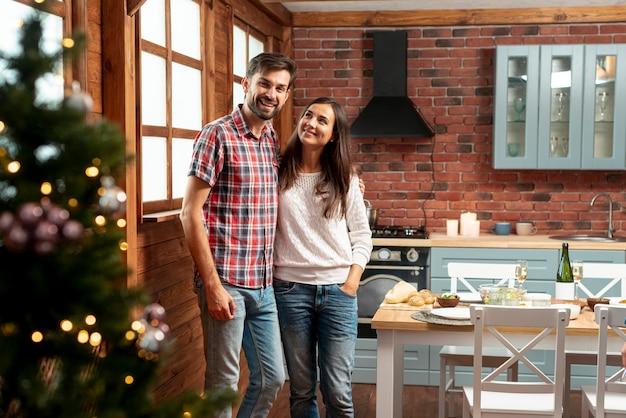 Coup moyen couple heureux posant dans la cuisine