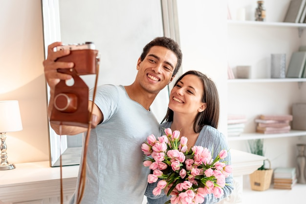 Coup moyen couple heureux en prenant une photo
