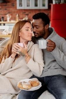 Coup moyen couple heureux avec des tasses