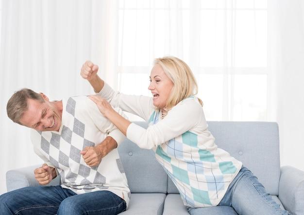 Coup moyen couple jouant sur le canapé