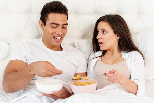 Coup moyen couple mangeant des céréales pour le petit déjeuner