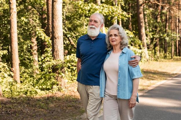 Coup moyen couple de personnes âgées marchant ensemble