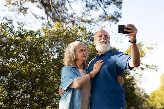Coup moyen couple de personnes âgées prenant selfie avec téléphone