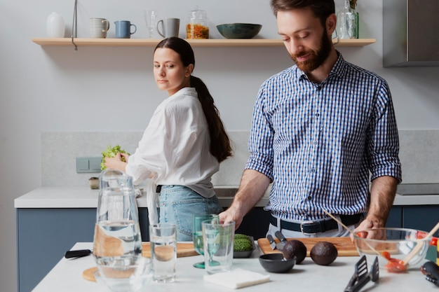 Coup moyen couple préparant de délicieux plats