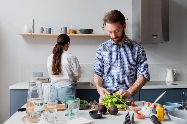 Coup moyen couple préparant de la nourriture savoureuse
