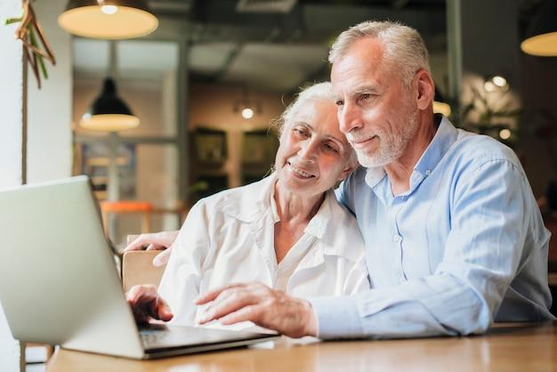 Coup moyen de couple regardant un ordinateur portable
