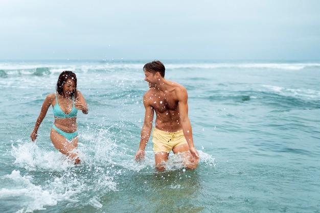 Coup moyen couple s'amusant au bord de la mer