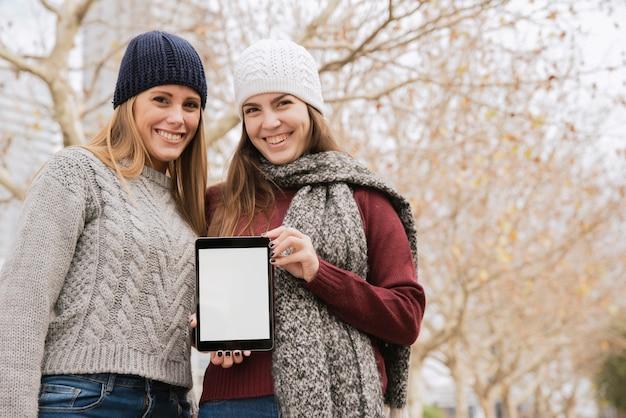 Coup moyen deux femmes élégantes tenant une tablette dans les mains