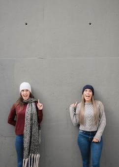 Coup moyen deux jeunes femmes souriantes pointant vers le haut