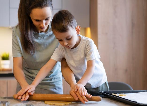 Coup moyen enfant et femme à l'aide de rouleau à pâtisserie