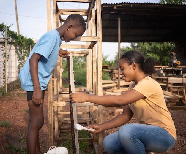 Coup moyen enfant et femme travaillant ensemble