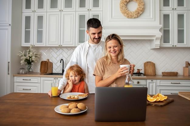 Coup moyen famille heureuse dans la cuisine