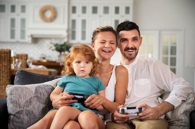 Coup moyen famille heureuse jouant à des jeux vidéo