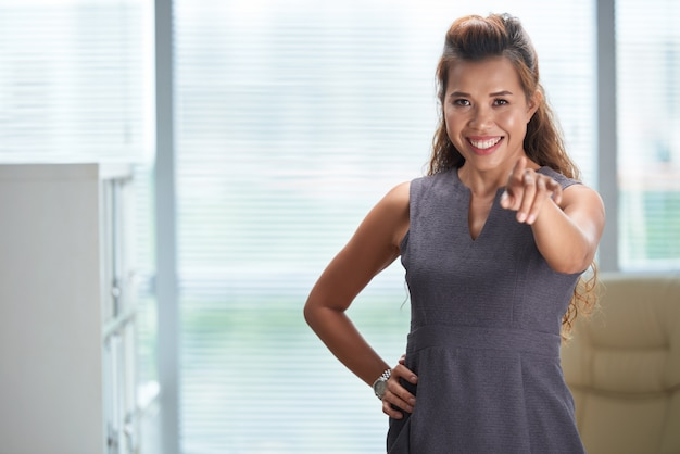 Coup moyen de femme d'affaires pointant à la caméra et souriant
