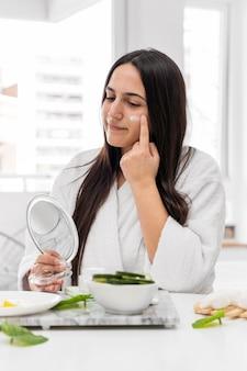 Coup moyen femme appliquant la crème pour le visage