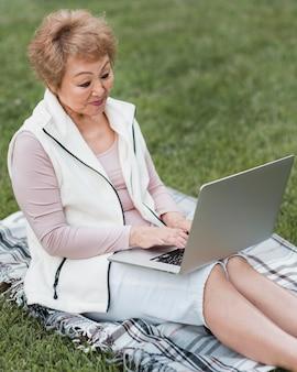 Coup moyen femme assise sur une couverture