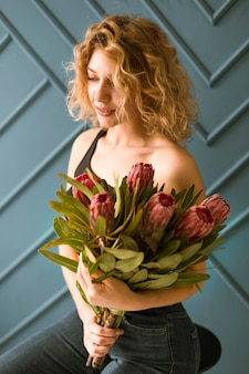 Coup moyen femme blonde avec bouquet de fleurs