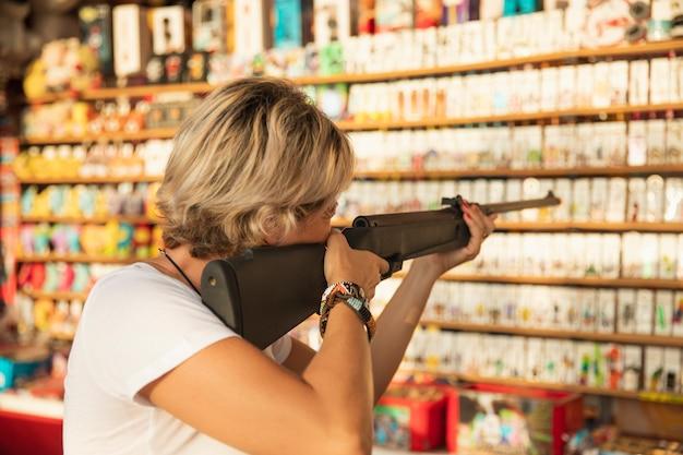 Coup moyen femme blonde jouant avec un fusil