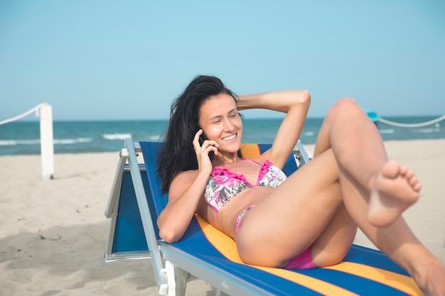 Coup moyen de femme sur une chaise de plage parlant au téléphone