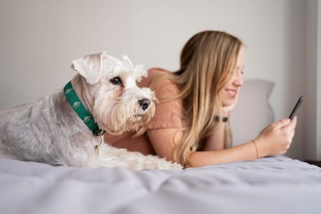 Coup moyen femme et chien au lit