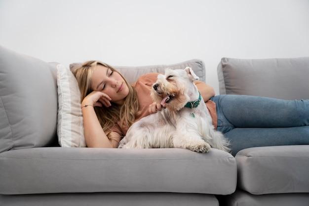 Coup moyen femme et chien sur canapé