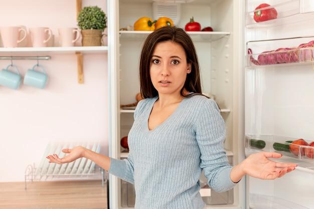 Coup moyen femme confuse dans la cuisine