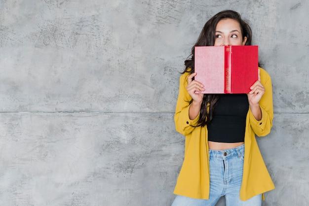 Coup moyen femme couvrant son visage avec un livre